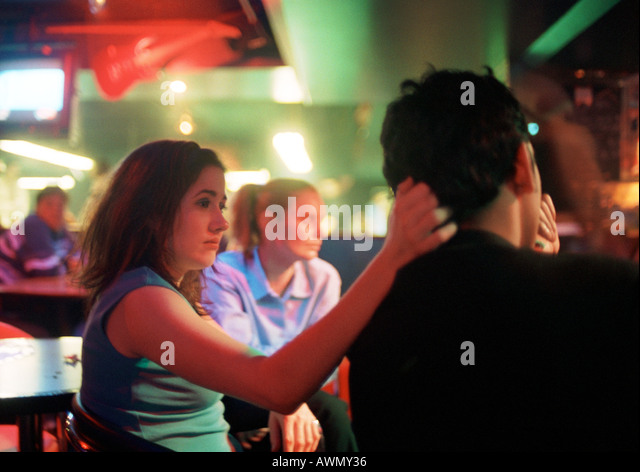 Young man and young woman sitting in bar - Stock-Bilder
