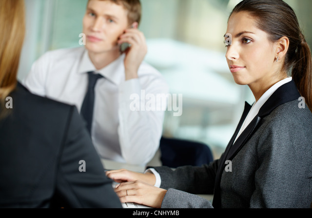 Young businesswoman working in the office together with her colleagues - Stock Image