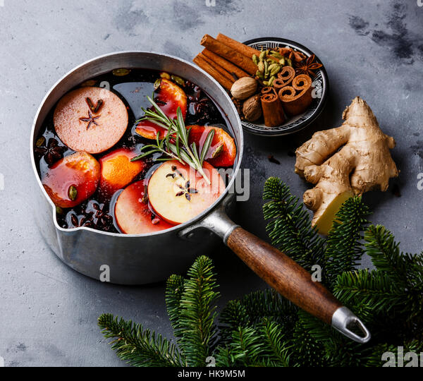 Mulled wine hot drink with citrus, apple and spices in aluminum casserole on concrete background - Stock Image