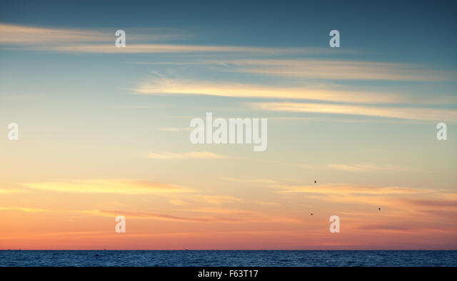 Colorful sunset sky over Atlantic ocean, natural background photo with warm tonal correction photo filter - Stock Image