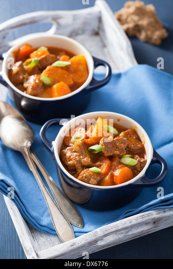 beef stew with potato and carrot in blue pots - Stock Image
