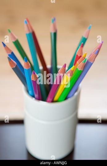Coloured pencils in a desk tidy - Stock Image