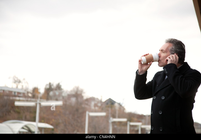 Mature man using cellphone and drinking coffee outdoors - Stock Image
