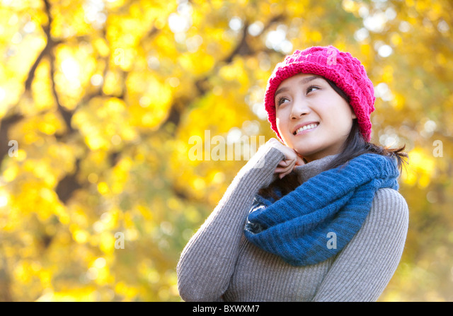 Young Woman in a Park in Autumn - Stock Image