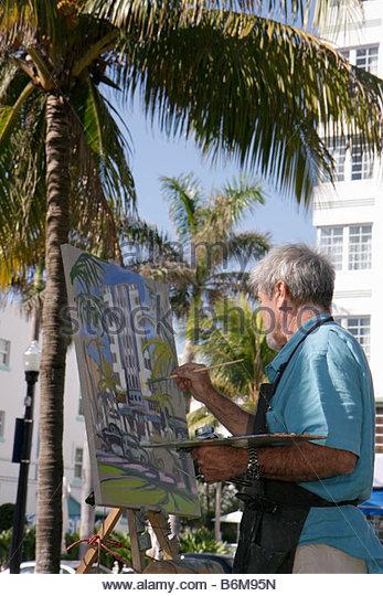 Miami Beach Florida Ocean Drive Lummus Park man senior easel canvas paintbrush painting art palm trees creativity - Stock Image