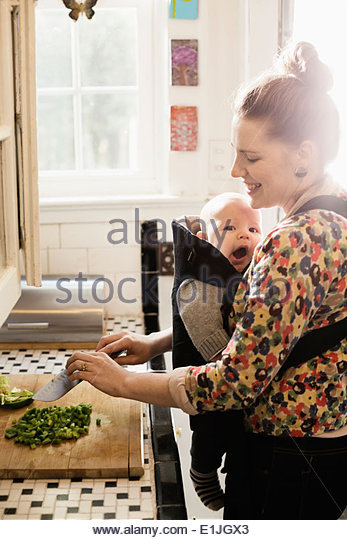 Mid adult mother preparing food with baby son in sling - Stock Image