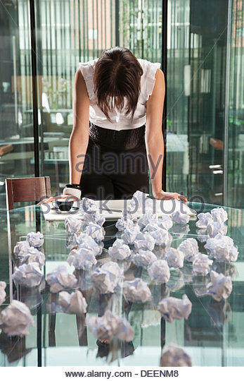 Businesswoman standing with crumpled papers in an office - Stock Image