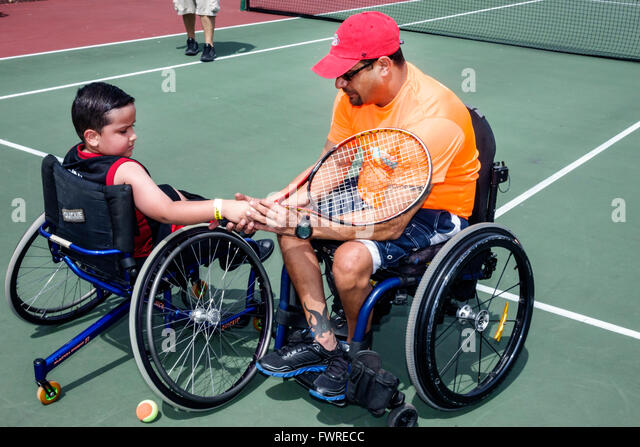 Florida FL Miami Tropical Park Paralympic Experience sports volunteer helping disabled tennis court wheelchair Hispanic - Stock Image