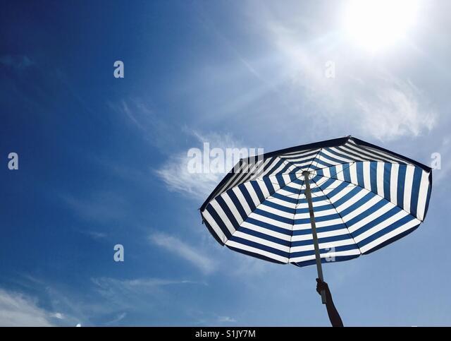 A hand holding an umbrella against a blue sky. Manhattan Beach, California USA. - Stock Image