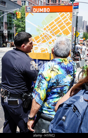 New York New York City NYC Brooklyn Dumbo neighborhood orientation sign map location man policeman officer giving - Stock Image