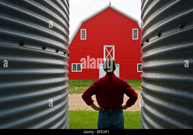 closeup of grain bins with man and red barn in the background near Torquay, Saskatchewan, Canada - Stock Image