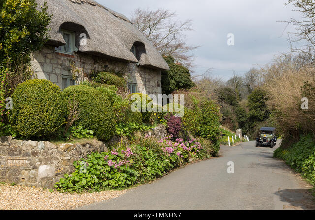 A vintage green car approaches up a narrow lane towards a thatched cottage in Godshill, Isle of Wight - Stock Image