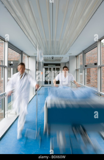Two healthcare workers pushing a hospital bed along a corridor - Stock Image