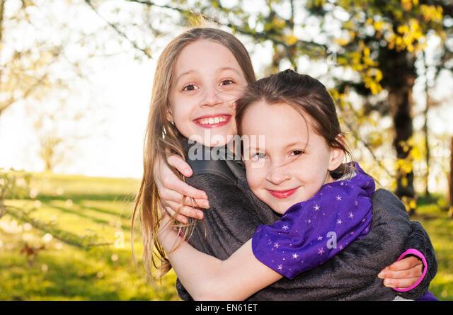 sisters smile hug - Stock Image