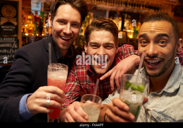 Male Friends Meeting For Evening Drinks In Cocktail Bar - Stock Image
