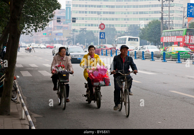 Man and woman cyclists with woman motorcyclist on a road in Chengdu, Sichuan Province, China. JMH4413 - Stock Image