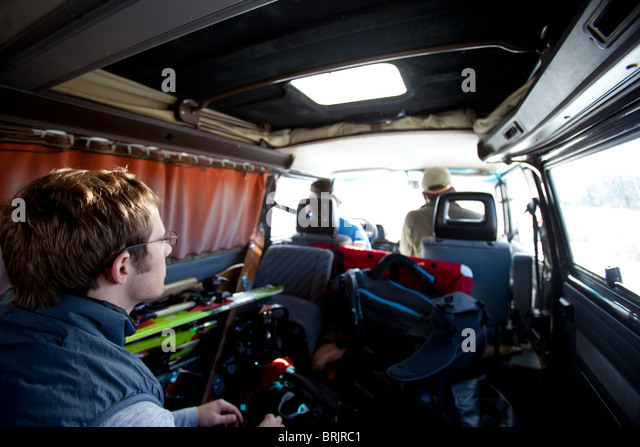 Three men riding in a classic van with ski equipment everywhere. - Stock Image