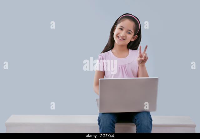 Little girl with a laptop pointing - Stock-Bilder