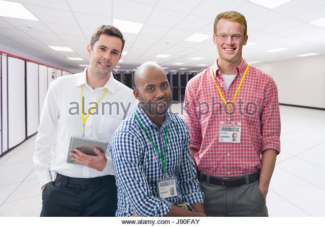 Portrait Of Technicians In Data Centre Standing By Servers - Stock-Bilder