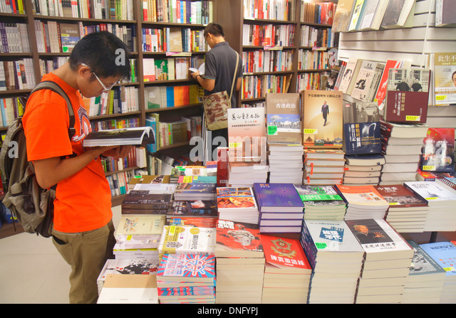 Hong Kong China Island Causeway Bay Yee Wo Street bookstore books sale display customer browsing Asian man - Stock Image