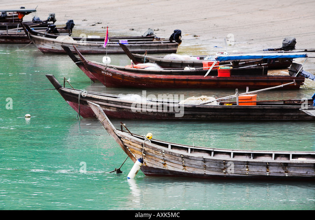 row of cones boats on water at shore water sand beach red blue white green brown - Stock Image