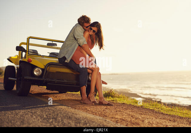 Romantic young couple sharing a special moment while outdoors. Young couple in love on a road trip. Couple embracing - Stock Image