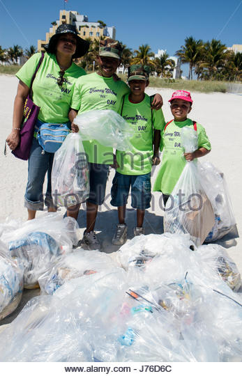Miami Beach Florida Honey Shine Green Day Black boy student volunteer clean-up collected trash litter pollution - Stock Image