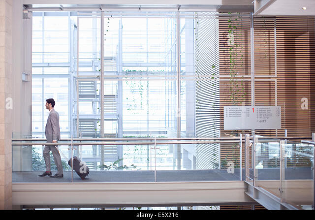 Young businessman with wheeled case in conference centre - Stock-Bilder