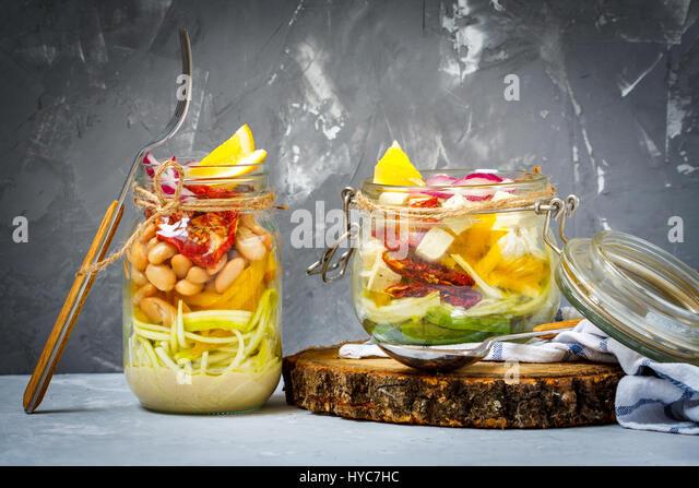 Homemade jar zucchini pasta with tofu, beans and vegetables. Detox, dieting, vegetarian, vegan, clean eating food - Stock Image