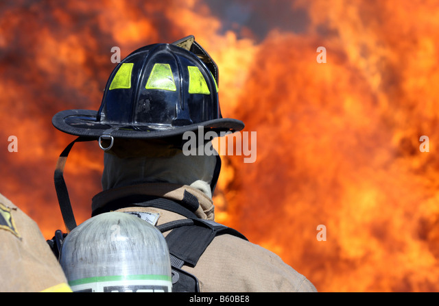 Firefighters in front of a blazing fire inferno - Stock-Bilder