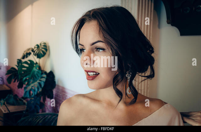 Thoughtful Young Woman Looking Away At Home - Stock-Bilder