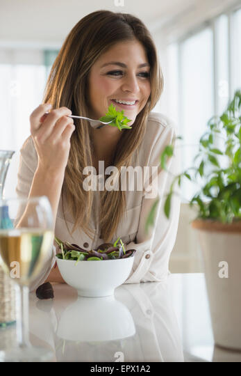 Young woman eating salad in living room - Stock-Bilder