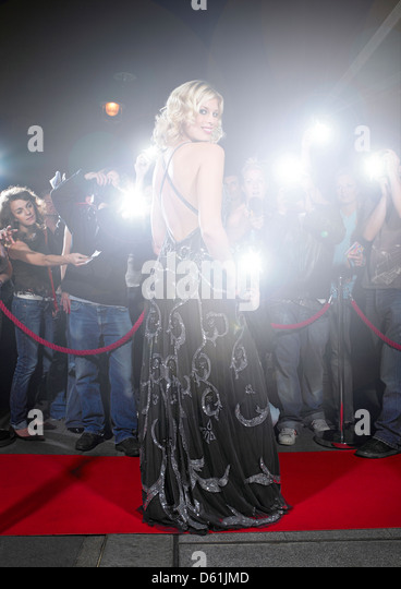 Portrait of young woman in gown posing for paparazzi the red carpet - Stock-Bilder