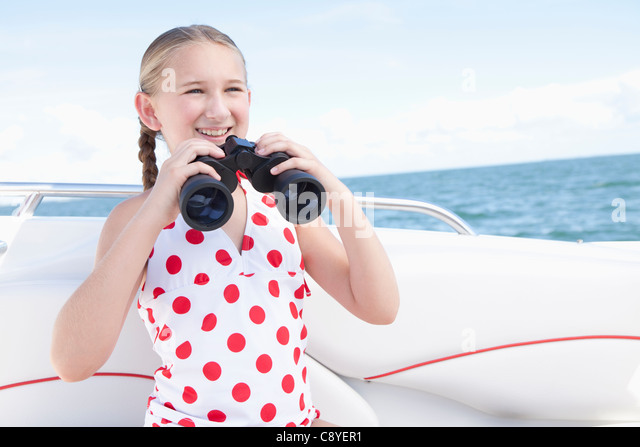 USA, Florida, St. Petersburg, Girl (10-11) on yacht holding binoculars - Stock Image