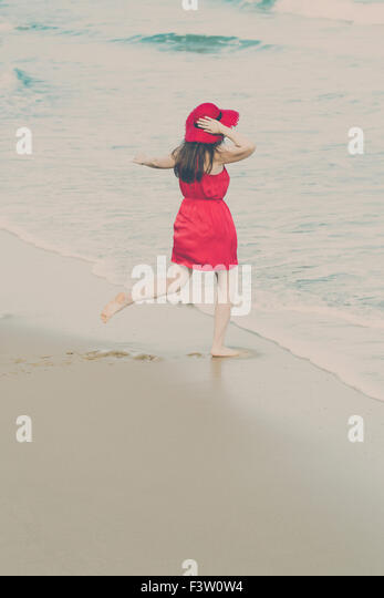 Young woman in a red dress on the beach - Stock-Bilder