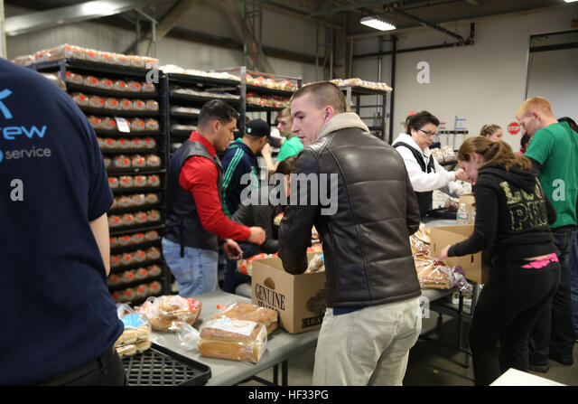 More than 20 Marines from U.S. Marine Forces Command and the II Marine Expeditionary Force help package bread at - Stock Image