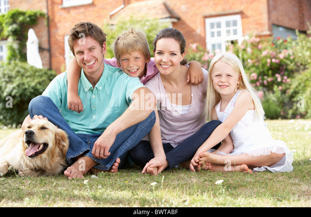 Family Sitting In Garden Together - Stock Image