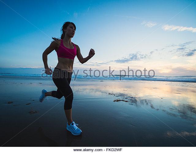 Young woman running on beach - Stock-Bilder