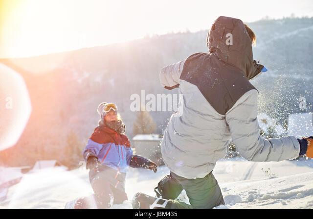 Playful couple enjoying snowball fight in sunny snowy field - Stock-Bilder