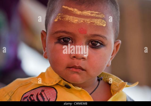Hindu child wearing bindi and painted yellow stripes on forehead in Varanasi, Uttar Pradesh, India - Stock Image