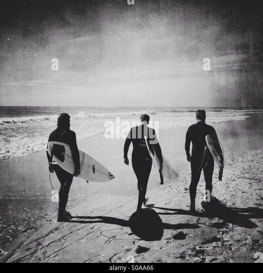 Three surfers walking down the beach. - Stock-Bilder