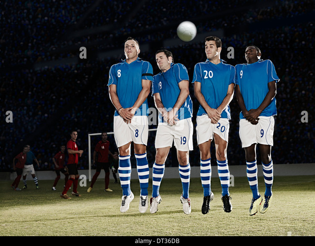 Soccer players jumping on field - Stock Image