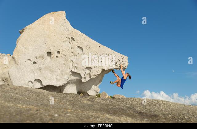 France, Corsica, Woman climbing on big single rock - Stock Image