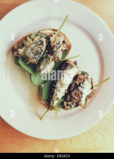 Canada, British Columbia, Greater Vancouver Regional District, Vancouver, Sardines on toast with fresh spinach greens - Stock Image