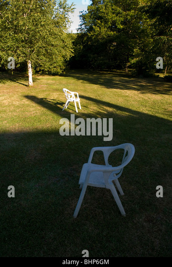 two white plastic garden chairs, one in shade and other in sunlight, sit apart on a lawn in a private garden - Stock Image