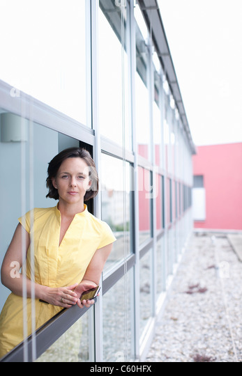 Businesswoman leaning out office window - Stock Image