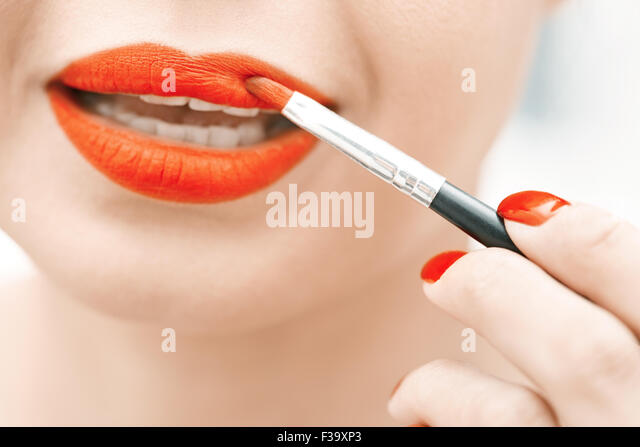 Woman applying red lipstick. Close-up view on face - Stock-Bilder