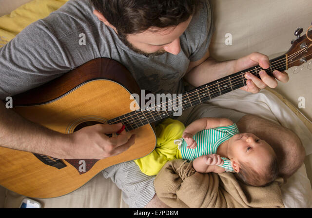 Father playing guitar for newborn daughter - Stock Image