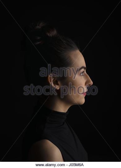 Profile portrait serious brunette woman against black background - Stock Image