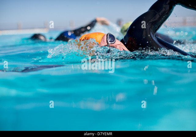 Triathletes in wetsuit splashing in pool - Stock-Bilder